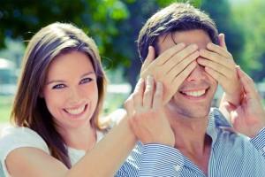 pareja-feliz-y-sonriente-ella-tapandole-los-ojos-a-el-detras-paisaje-desenfocado
